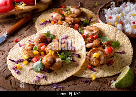 Delicious spicy shrimp tacos with sriracha mayo on a rustic wood table top. - Stock Photo
