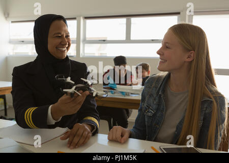 Female pilot teaching about model drone to student - Stock Photo