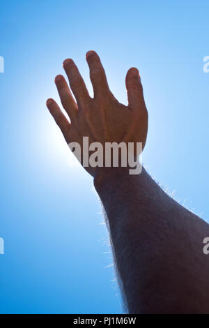 an adult male's arm and hand, backlight by bright sunshine, reach away from camera towards a clear blue sky - Stock Photo