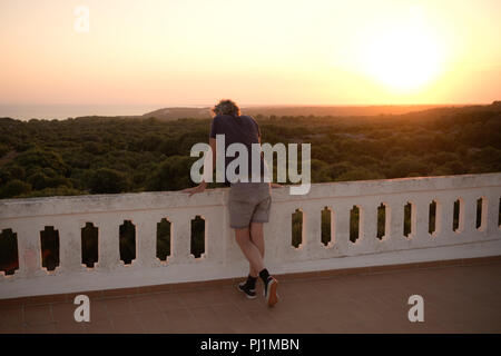 rear view of adult male leaning on roof top terrace balustrade of villa in Menorca, looking out across landscape at sunset - Stock Photo