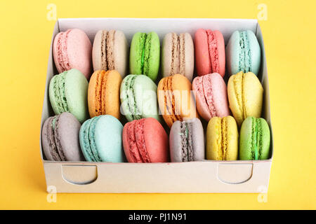 colorful macarons in box on yellow white background closeup. - Stock Photo