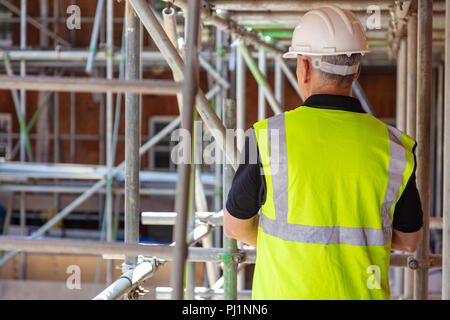 Rear view of male builder construction worker on building site wearing hard hat and hi vis vest - Stock Photo