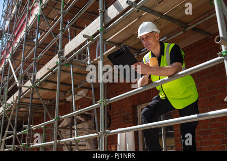 Male builder foreman, construction worker or architect on site holding a clipboard and drinking a mug of coffee or tea - Stock Photo