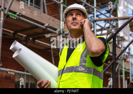 Male builder foreman, worker or architect on construction site holding building plans and talking on his cell phone - Stock Photo