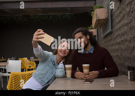 Couple taking selfie at outdoor cafe - Stock Photo