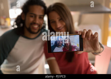 Couple taking selfie in cafe - Stock Photo
