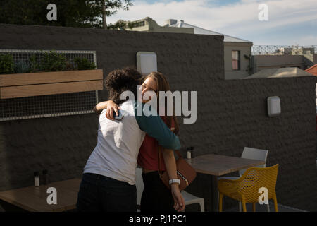 Couple hugging each other in outdoor cafe - Stock Photo