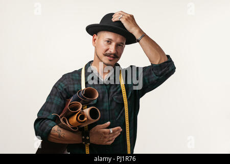 Artisan of leather in creative black hat posing with leather goods in studio. - Stock Photo