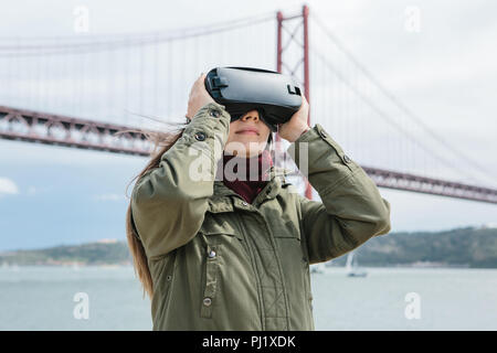 Young beautiful girl wearing virtual reality glasses. 25th of April bridge in Lisbon in the background. The concept of modern technologies and their use in everyday life. - Stock Photo