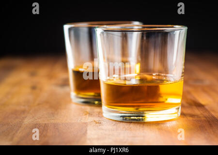 Glass of alcoholic drink wooden table. Whiskey in glass. - Stock Photo