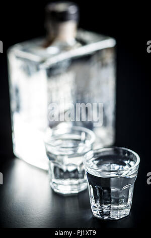 Vodka in shot glass. Transparent alcohol on black table. - Stock Photo