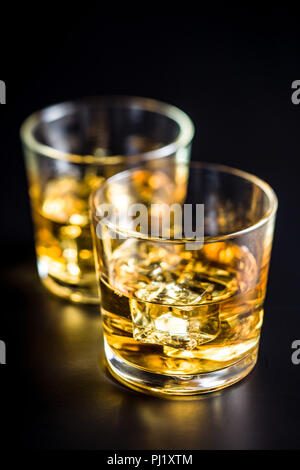 Glass of alcoholic drink with ice cubes on black table. Whiskey in glass. - Stock Photo
