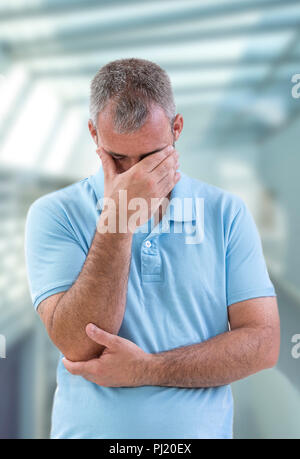 Depressed Concept. Displeased young man in blue shirt covering his eyes Concept of negative emotion. Problems at work or in family - Stock Photo