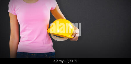 Composite image of woman holding hard hat against grey background - Stock Photo