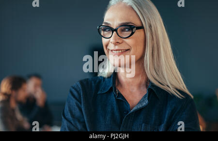 Close up portrait of senior business woman wearing eyeglasses standing in office. Mature female in office looking at camera smiling. - Stock Photo