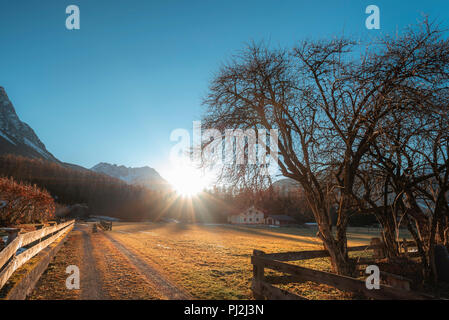 Landscape with the sun and its rays shining and warming the Austrian Alps, the leafless trees, on a sunny day of early winter, in Ehrwald, Austria. - Stock Photo