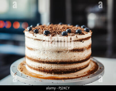 Close up of chocolate cake with cream cheese and berries. - Stock Photo