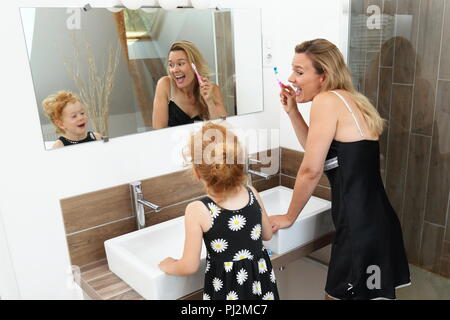 Mother and Daughter having fun during brushing teeth in a modern Bathroom - Stock Photo