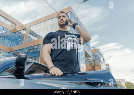 Close up of man getting out of the black car and talking by mobile phone. - Stock Photo