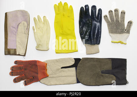 mix of working protective gloves: textile (for gardening, with rubber dots, nitrile coated); rubber (for cleaning (long), medical); and mittens - Stock Photo