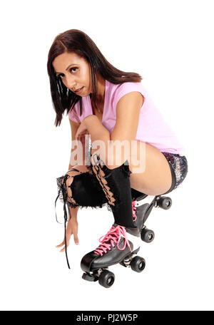 A pretty woman with roller skates and shorts crouching on the floor resting from her dance, isolated for white background - Stock Photo
