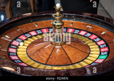 Roulette spinning, in movement, during a demo game. Roulette is a gambling and betting casino game  Picture of a roulette turning fast with a white ba - Stock Photo
