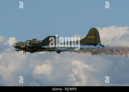 Sally B, the preserved Boeing B-17 Flying Fortress bomber trailing smoke during it's display at Dunsfold Wings & Wheels, UK on the 25th August 2018. - Stock Photo
