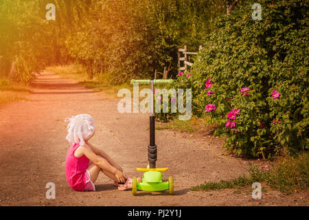 A little girl is sitting on the road next to a scooter in the countryside in the rays of a bright warm sun - Stock Photo