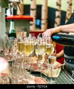 Bartender pouring champagne or spakling wine into glass, close-up in glasses in restaurant. - Stock Photo