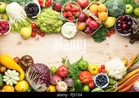 Fresh organic fruits vegetables berries, cherries apricots strawberries cabbage broccoli cauliflower squash tomatoes carrots spring onions beans beetroot, pepper, copy space, top view, selective focus - Stock Photo