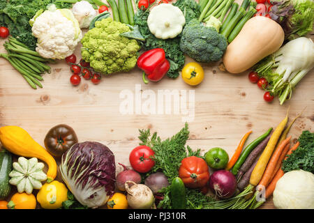 Fresh farm produce, organic vegetables and herbs on pine wooden table, healthy background, copy space for text in the middle, top view, selective focus - Stock Photo