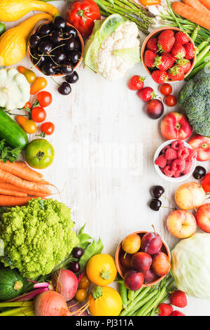 Fresh summer fruits vegetables berries, apples cherries peaches strawberries cabbage broccoli cauliflower squash tomatoes carrots spring onions beans beetroot, copy space, top view, selective focus - Stock Photo
