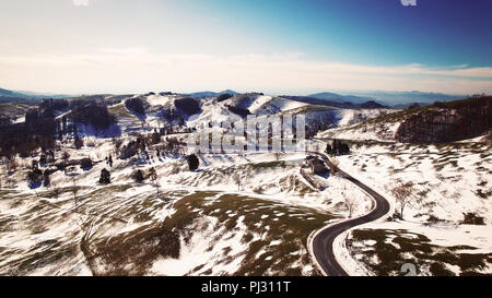 Road winds through the hills partially covered with snow. - Stock Photo