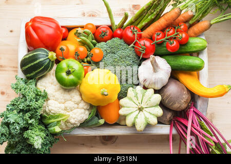 Fresh organic vegetables in a white tray on wooden pine table, top view, selective focus - Stock Photo