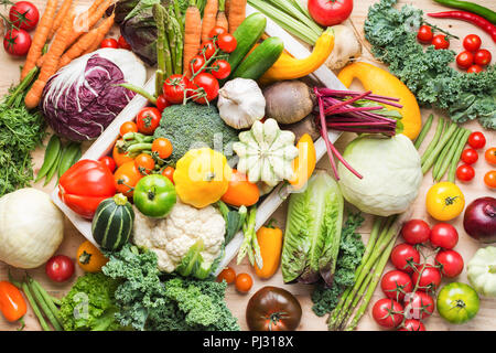 Assortment of fresh colorful organic vegetables in white tray on wooden pine table, food background, top view, selective focus - Stock Photo