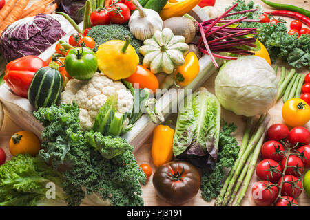 Assortment of fresh colorful organic vegetables in white tray on wooden pine table, food background, selective focus
