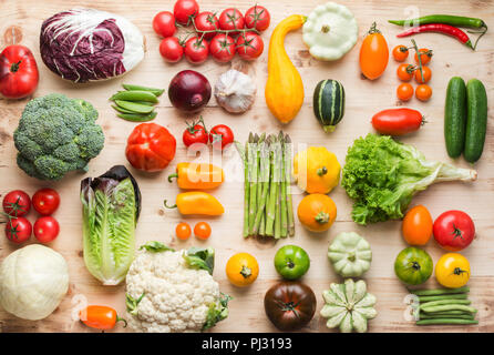 Assortment of fresh colorful organic vegetables on wooden pine table, creative food background, grid, top view, selective focus - Stock Photo