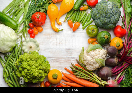 Fresh farm produce, colorful frame made of organic vegetables and herbs on white wooden background, healthy background, copy space for text, top view, selective focus - Stock Photo