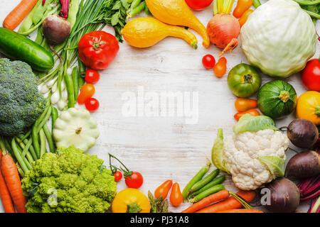 Fresh farm produce, colorful frame made of assorted vegetables and herbs on white wooden background, healthy background, copy space for text in the middle, top view, selective focus - Stock Photo