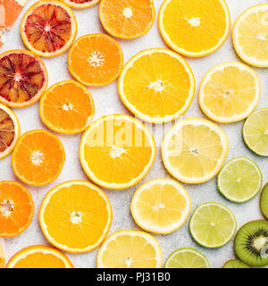Different varieties of citrus fruits, oranges, lemons, limes, kiwis arranged in the rows, diagonal, square. Colorful background, top view - Stock Photo