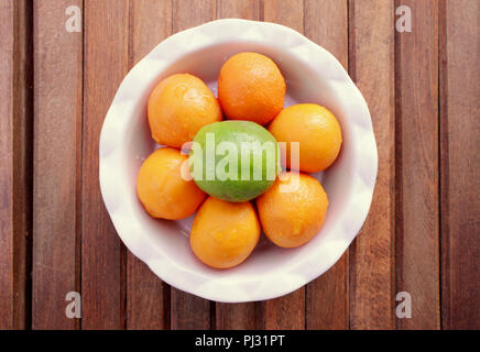 A round white bowl of six mandarin oranges and one green lime sits on a wood slat background. - Stock Photo