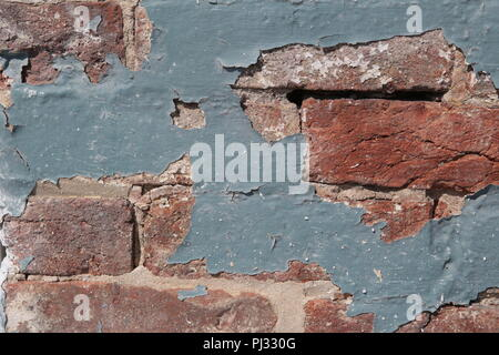 old paint peeling from brick wall - Stock Photo