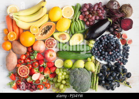 Healthy eating concept, assortment of rainbow fruits and vegetables, berries, bananas, oranges, grapes, broccoli, beetroot on the off white table arranged in a rectangle, top view, selective focus - Stock Photo