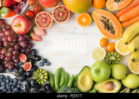 Healthy eating, varieity of fruits and vegetables in rainbow colours on the off white table arranged in a frame with copy space, vertical top view, selective focus - Stock Photo