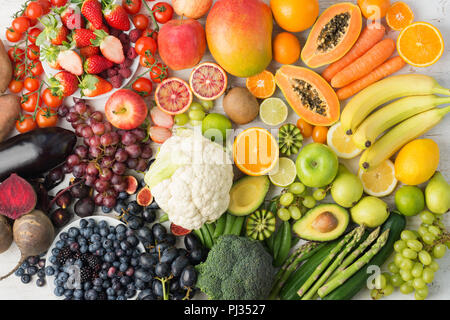 Healthy eating background, assortment of different fruits and vegetables in rainbow colours on the off white table arranged in a rectangle, top view, selective focus - Stock Photo