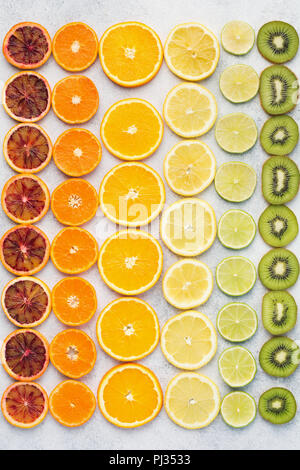 Different varieties of citrus fruits, oranges, lemons, limes, kiwis arranged in the rows. Colorful background, top view - Stock Photo
