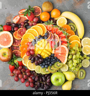 Colorful cut fruits platter in rainbow colors oranges grapes mango strawberries kiwis blueberries grapefruit on the grey concrete table arranged in circle, top view, selective focus - Stock Photo