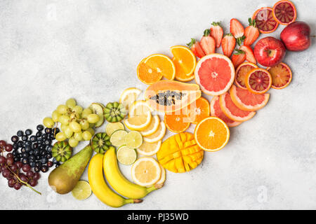 Above view of healthy fruits in rainbow colours, strawberries, mango, grapes, bananas, grapefruit on the off white table, copy space for text, selecti - Stock Photo