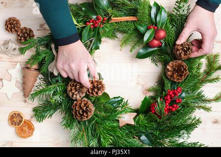 Hands arranging and decorating handmade Christmas wreath with fir branches, pine cones, berries, baubles on the natural wooden table, top vew, selecti - Stock Photo