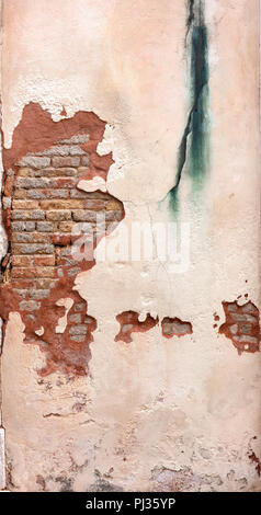 white wall of lime with damage showing the interior of reddish bricks and green paint stain - Stock Photo